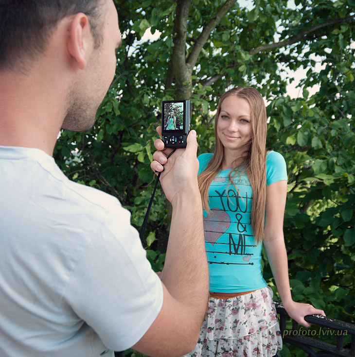 Photographer takes a girl on a digital compact camera