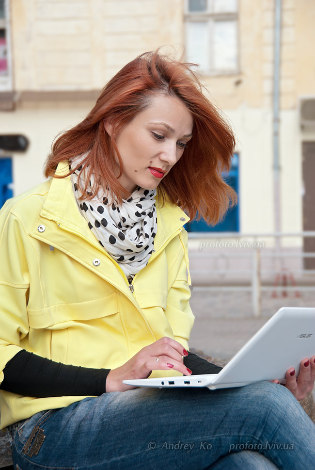 A girl in a yellow jacket with a netbook on your lap for a photo copyrights author