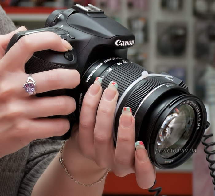 Photographer holding a camera in the hands of the lens