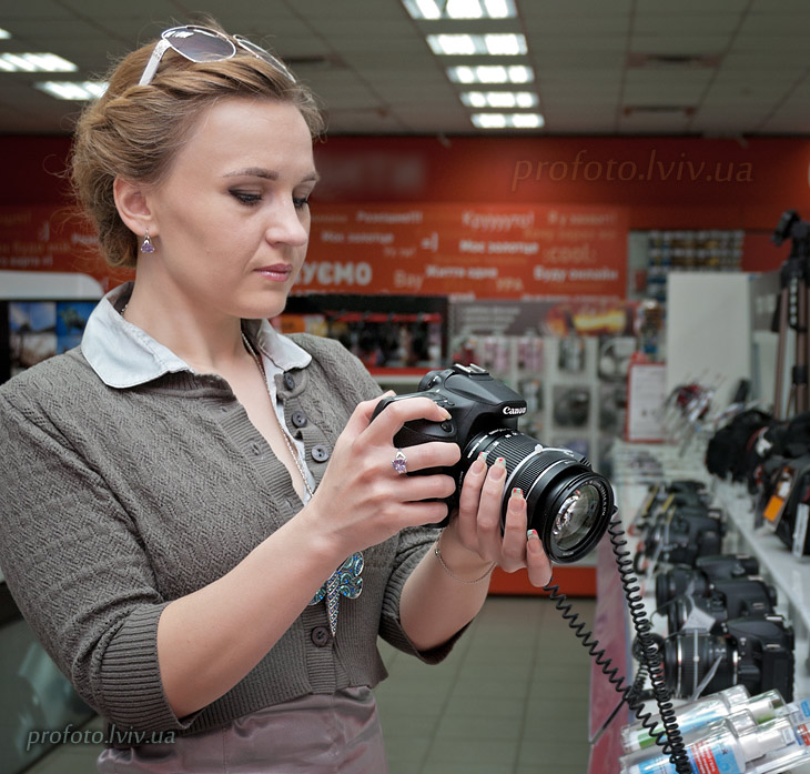 A girl holding a digital camera Canon